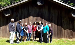 CNAY staff Amber Richardson with Siletz tribal leadership and program staff. Group photo in front of Siletz cedar dance house.